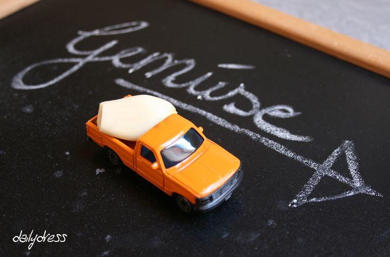 Knoblauchzehe auf der Pritsche vom Spielzeugauto unterwegs zum Kinderteller